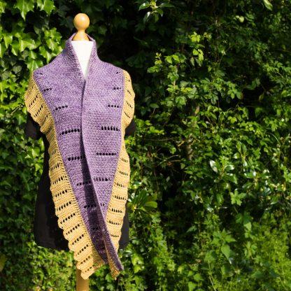 A Tunisian crochet shawl in purple and gold yarn