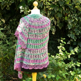 A large, lacey crochet shawl in pinks and greens